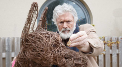 Patrick Bergin places a commemorative tag on a sculpture at the Dog's Trust legacy garden