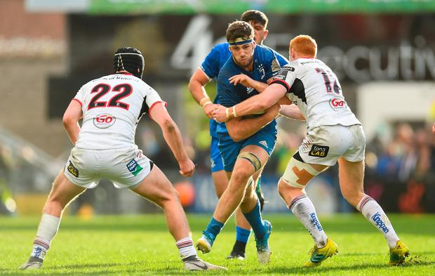 Caelan Doris of Leinster is tackled by Jack Owens, left, and Peter Nelson of Ulster. Photo: Ramsey Cardy/Sportsfile