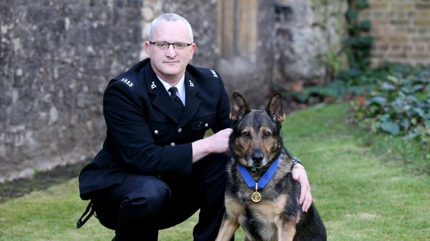 Handler PC Dave Wardell and his retired police dog Finn (Jonathan Brady/PA)
