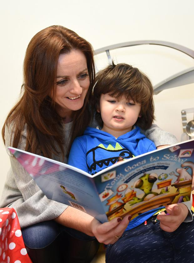 HELPING HAND: Author and tutor Valerie Sheehan and Daniel O'Connell read her book 'Tony Goes To School'