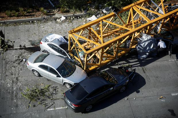A member of the Seattle police department inspects one of the cars crushed by part of a construction crane on Mercer Street, which killed four people and injured several others in Seattle, Washington, U.S. April 27, 2019. REUTERS/Lindsey Wasson