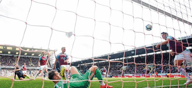 Game of inches: Burnley's Matthew Lowton unsuccessfully attempts to prevent Sergio Aguero's strike from crossing the line. Photo: Andrew Yates/Reuters