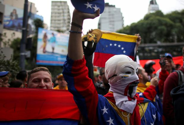 A masked Venezuelan demonstrator gestures during a protest in support of Venezuela's opposition leader Juan Guaido, who many nations have recognized as the country's rightful interim ruler, outside the Venezuelan Embassy in Buenos Aires REUTERS/Agustin Marcarian
