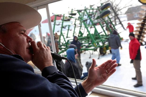 Auctioneer Dan Sullivan of Sullivan Auctioneers calls the bids as a retiring farmer's equipment is auctioned at Jim & Karen Taphorn's farm near Beattie, Kansas, U.S., February 27, 2019. Picture taken February 27, 2019. REUTERS/Lane Hickenbottom