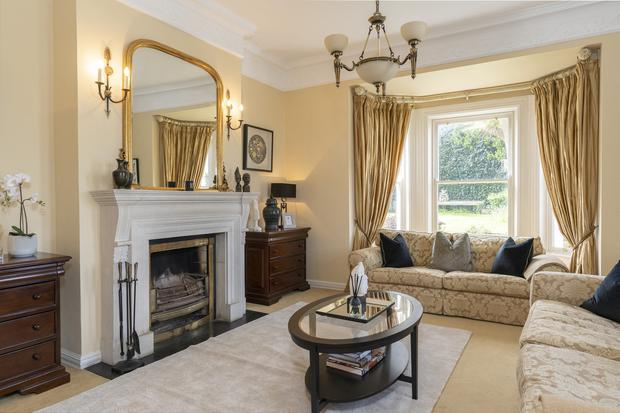The drawing room features a bay window and stone fireplace