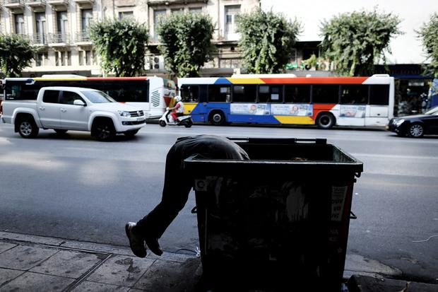 Economic disaster: A man searches the contents of a public bin on a street in Thessaloniki, Greece, last June. Photo: Konstantinos Tsakalidis/Bloomberg