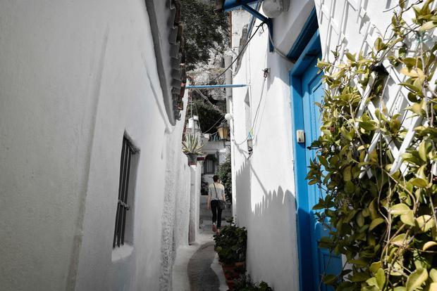 Winding road: A tourist makes her way along a passageway in the tiny Anafiotika district of Athens. Photo: AFP/Getty Images