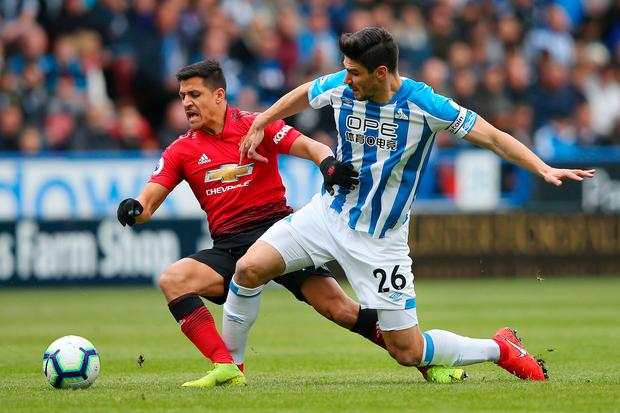 Manchester United 's Alexis Sanchez is challenged by Huddersfield Town's Christopher Schindler. Photo: Getty Images