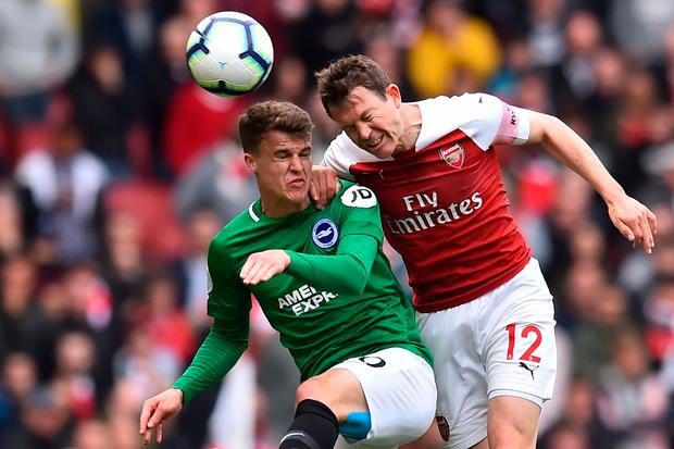 Brighton's Solly March and Arsenal's Stephan Lichtsteiner rise for the ball. Photo: Getty Images