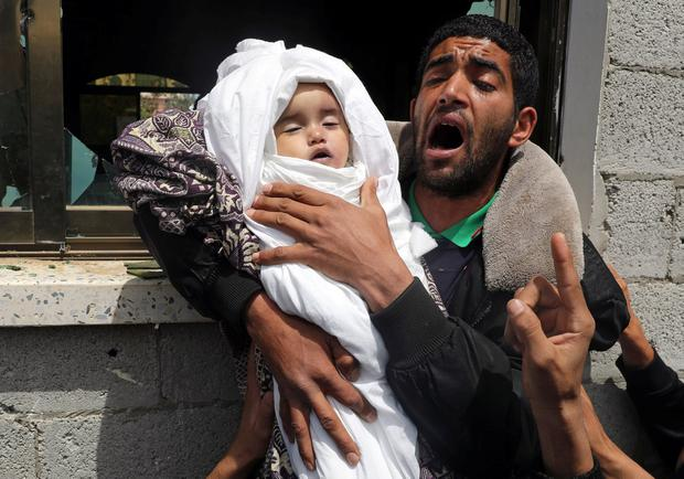 Grief: A relative of 14-month-old Palestinian baby Seba Abu Arar carries her body during her funeral in Gaza after Israeli air strikes on Saturday. Photo: Reuters