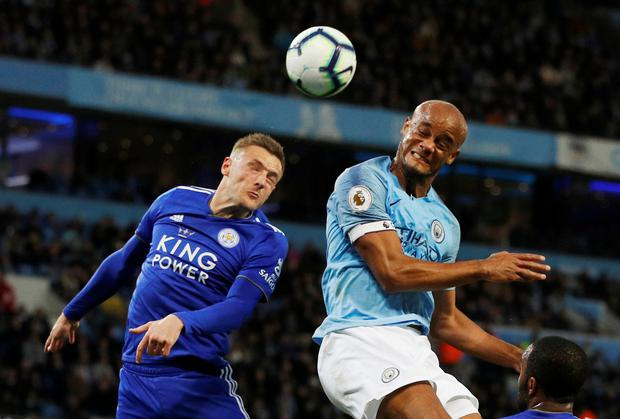 Manchester City's Vincent Kompany rises with Leicester City's Jamie Vardy. Photo: Reuters