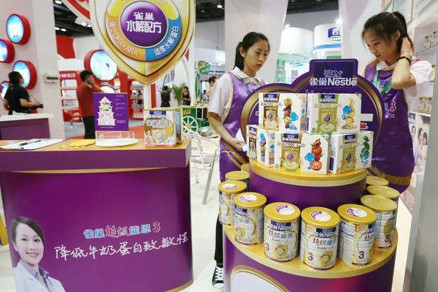 Staff members are seen at the booth of Nestle promoting its baby food and NAN infant formula products at a maternity and baby industry fair in Beijing, China July 25, 2013. Picture taken July 25, 2013. REUTERS/Stringer