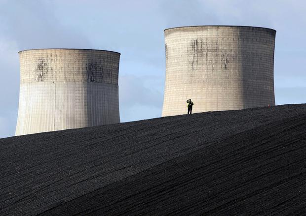 A security guard watches from a coal heap during a climate change protest at Ratcliffe Power Station at Ratcliffe-on-Soar, central England October 17, 2009. REUTERS/Darren Staples/File Photo