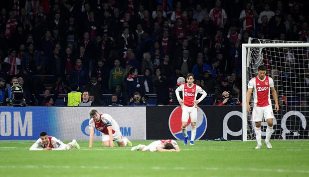 Ajax players lie down dejected after conceding a last minute goal to send them out of the Champions League. Photo: REUTERS/Piroschka Van De Wouw