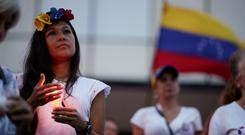 Stand-off: A woman at a vigil held for victims of the violence in Caracas. Photo: REUTERS/Ueslei Marcelino