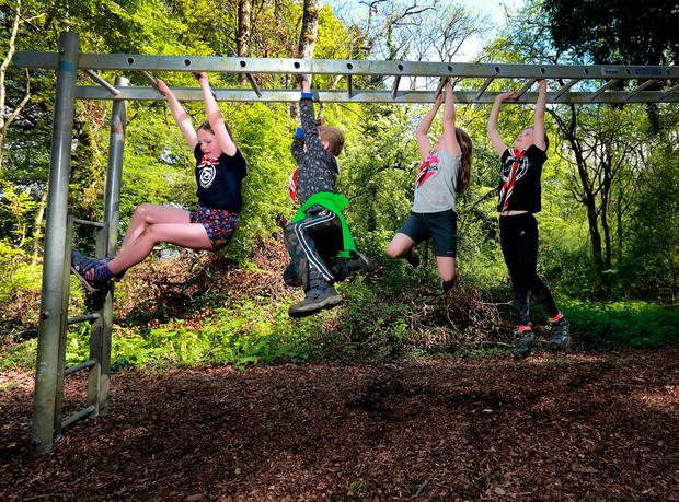 Members of the 73rd Raheny scout troop ,Carragh Hardiman, Ronan O Sullivan, Lorea Hurley and Siún Kelly, tackle the monkey bars during the obstacle course, at their camping weekend at Portlick Scout Campsite in Westmeath. Picture:Frank McGrath