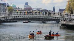 Summer sports: Rowers at the Ha'Penny Bridge on the river Liffey, Dublin. Photo: Collins