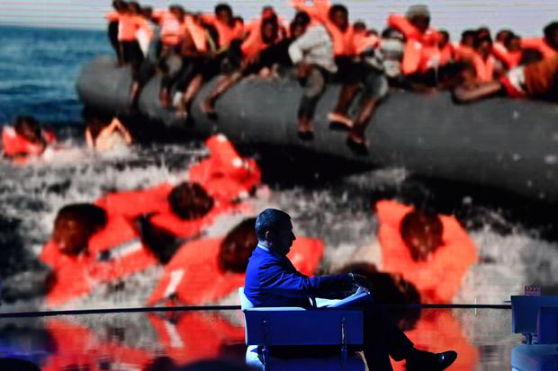 Border controls: Italy's Deputy Prime Minister Matteo Salvini on an Italian talk show, with a picture of migrants in the background. Last week Salvini inspected the 175km-long barbed wire fence designed to prevent migration to Hungary from Serbia. Photo: ANDREAS SOLARO/AFP/Getty Images