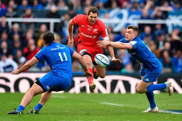 Saracens' English full-back Alex Goode (C) kicks the ball between Leinster's New Zealand wing James Lowe (L) and Leinster's Irish centre Garry Ringrose (R) . Photo: AFP/Getty Images