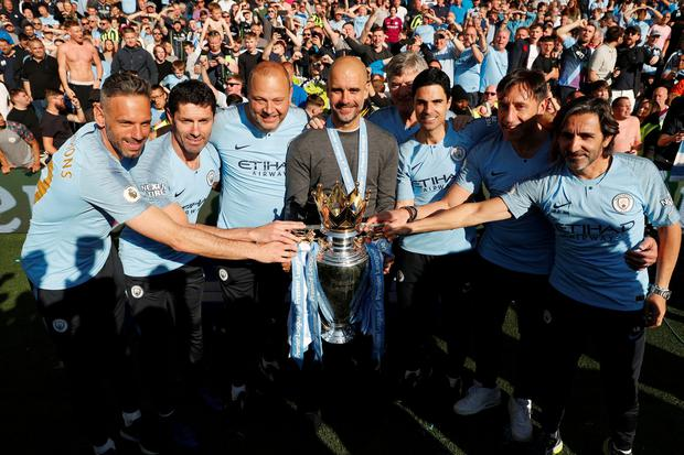 Manchester City goalkeeper coaches Richard Wright and Xabi Mancisidor, assistant coach Rodolfo Borrell, manager Pep Guardiola, assistant coach Mikel Arteta, coach Carles Planchart and assistant coach Lorenzo Buenaventura pose with the trophy as they celebrate winning the Premier League. Action Images via Reuters/John Sibley