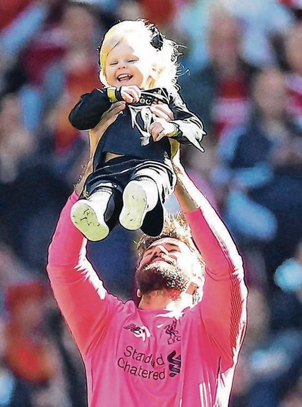 Alisson provides a safe pair of hands for his daughter during the post-game lap of honour. Photo: Carl Recine/Action Images via Reuters