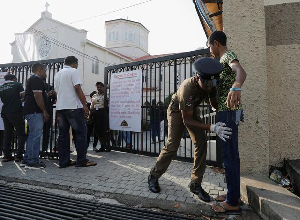 Precaution: A police officer searches a worshipper at the entrance to St Theresa's Church in Colombo. Photo: Reuters/Dinuka Liyanawatte