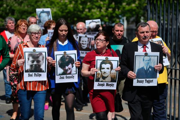 Families of those who died in the Ballymurphy Massacre hold images of their loved ones outside Laganside Court in Belfast as the inquest continues. Photo: Niall Carson/PA Wire