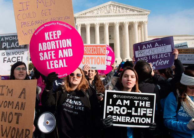 In this file photo taken on January 18, 2019, pro-choice activists hold signs alongside anti-abortion activists participating in the