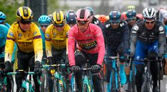 Overall leader and Pink Jersey holder Team Jumbo rider Slovenia's Primoz Roglic (C) rides through the rain with teammates as they take part in stage five of the 102nd Giro d'Italia - Tour of Italy - cycle race, 140kms from Frascati to Terracina on May 15, 2019. (Photo by Luk BENIES / AFP)