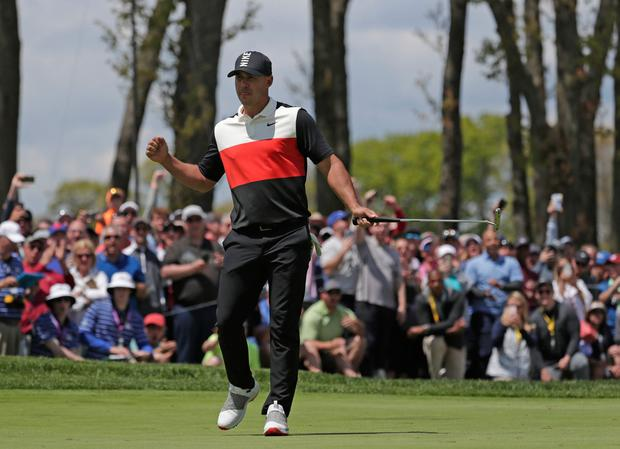 Brooks Koepka reacts after sinking a putt on the ninth green on the first day