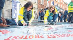 Health protest: Psychiatric Nurses Association ambulance members Tina Martin from Donegal and Siobhán Kelleher from Cork prepare their posters before protesting outside Leinster House over their right to represent-ation by a trade union of their choice. Photo: Frank McGrath