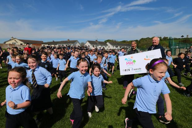 Pupils and teachers from St Patrick's NS in Slane run in the Daily Mile, watched by Lisa O'Dowd from Meath Sports Partnership and Frank Greally, Athletics Ireland's Daily Mile ambassador. Photo: David Conachy