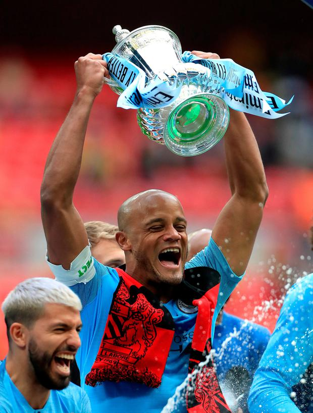 Manchester City's Vincent Kompany celebrates with the trophy after winning the FA Cup Final at Wembley Stadium, London. Photo credit: Mike Egerton/PA Wire.