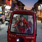 Street scene: A woman and her child ride an electric tricycle in the old town of Luoyang in Henan province, China. Photo: REUTERS