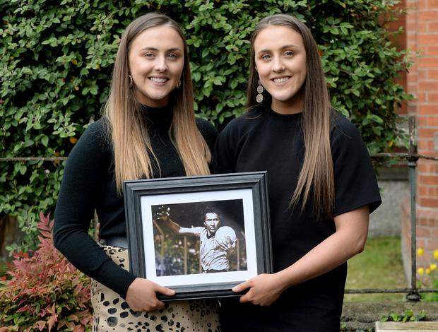 Tribute: Twins Laura and Niamh Leacy, who are nieces of the late Anton O'Toole, hold a photo of their uncle playing for Dublin at the funeral home where he is reposing in Dublin. Photo: Caroline Quinn