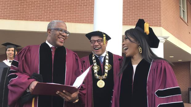 Robert F Smith, left, laughs with David Thomas, centre, and actress Angela Bassett at Morehouse College (Bo Emerson/Atlanta Journal-Constitution/AP)