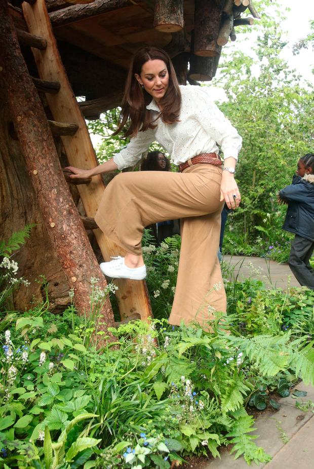 Britain's Catherine, Duchess of Cambridge climbs a ladder into a treehouse as she visits the 'Back to Nature Garden' garden, that she designed along with Andree Davies and Adam White, during her visit to the 2019 RHS Chelsea Flower Show in London on May 20, 2019