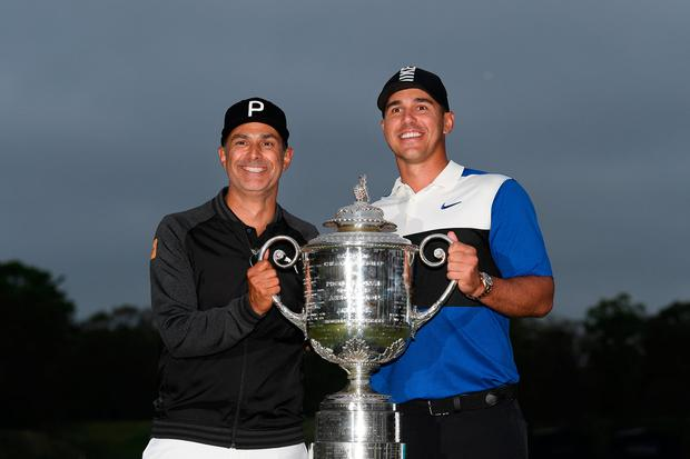 Brooks Koepka poses with caddie Ricky Elliott – who is from Portrush – and The Wanamaker Trophy after winning the PGA Championship at Bethpage Black on Sunday. Photo by Stuart Franklin/Getty Images