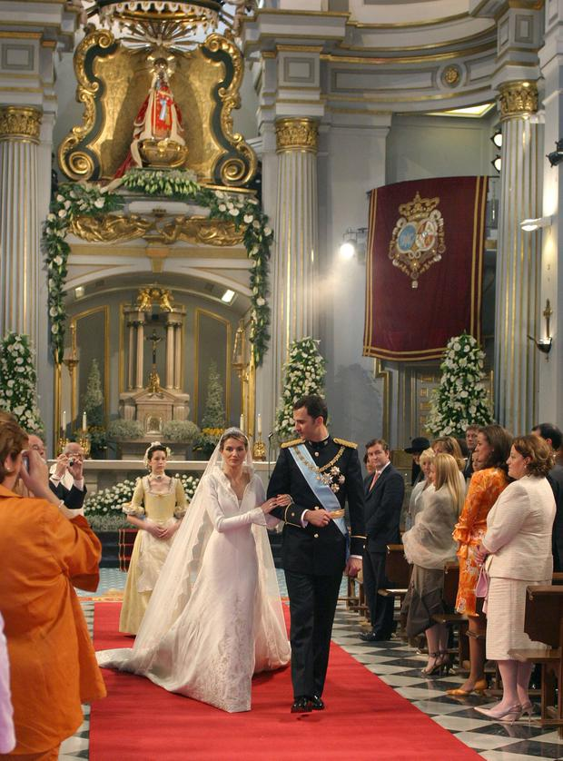 Spain's Crown Prince Felipe de Bourbon walks next to his bride, princess Letizia Ortiz after their wedding ceremony in Almudena cathedral May 22, 2004 in Madrid. (Photo by Lavandeira jr/Pool/Getty Images)