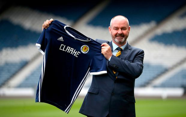 New Scotland manager Steve Clarke holds up a shirt during the press conference at Hampden Park, Glasgow today. Jane Barlow/PA Wire