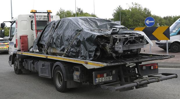 A burnt out car is removed from the scene of a shooting at Walshestown, Co. Dublin. Picture credit; Damien Eagers / INM