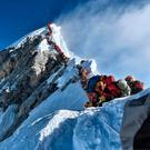 Mountain climbers lining up to stand at the summit of Mount Everest. Photo: AFP PHOTO / PROJECT POSSIBLE