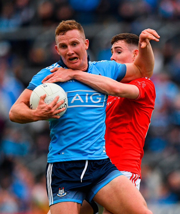 Ciarán Kilkenny of Dublin is tackled by Ciarán Downey of Louth. Photo: Eóin Noonan/Sportsfile