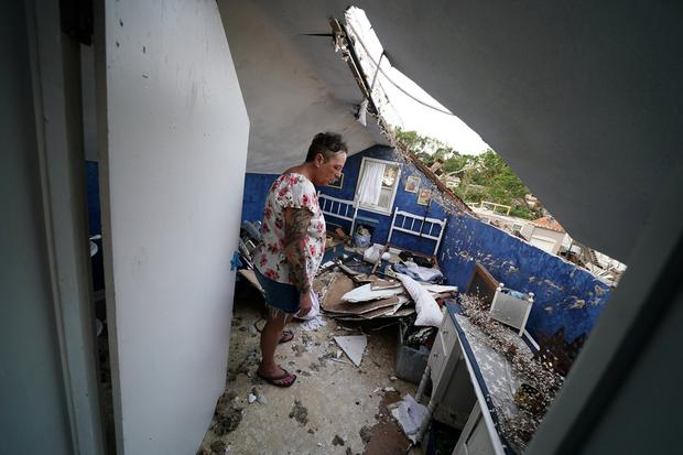 Destroyed: Gwen McGeorge looks at the hole in the roof of her home in Jefferson City, Missouri. Photo: Reuters