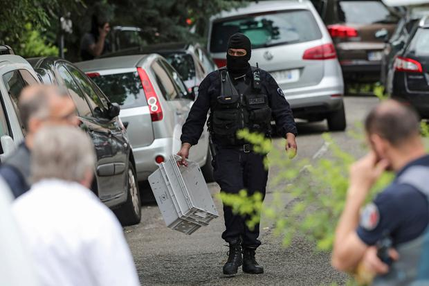 A hooded police officer holds a box during searches at a suspect's home following the blast in Lyon. Photo: AP