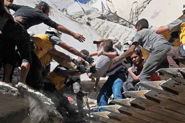 Saved: Volunteers rescue a child from the rubble of a building hit by an air strike in Ariha. Photo: AFP/Getty Images