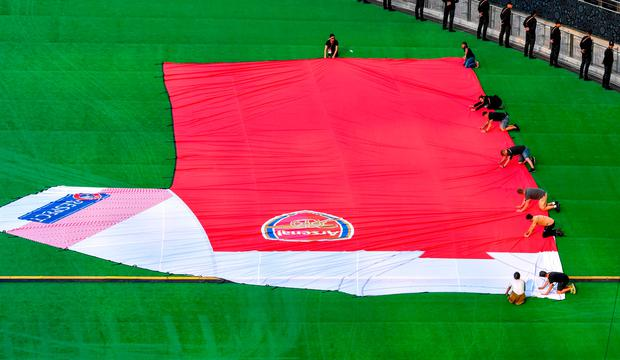 Volunteers pull a giant Arsenal jersey on the pitch inside Baku Olympic Stadium ahead of tomorrow's Europa League final against Chelsea. Photo: Getty Images