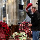 A mourner pays his respects at the coffin of Austrian motor racing greatNikiLauda during his funeral at St Stephen's cathedral in Vienna, Austria this morning. Photo: Reuters/Lisi Niesner