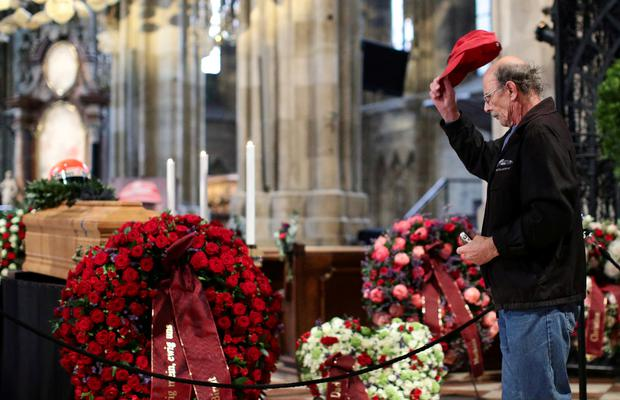 A mourner pays his respects at the coffin of Austrian motor racing great Niki Lauda during his funeral at St Stephen's cathedral in Vienna, Austria this morning. Photo: Reuters/Lisi Niesner