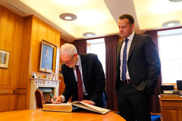 Handout photo issued by MerrionStreet of Jeremy Corbyn signing the visitors' book as Taoiseach Leo Varadkar welcomes him to the Government Buildings in Dublin Photo: MerrionStreet/PA Wire
